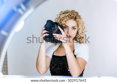 Photographer girl shooting images in studio. Attractive blonde woman taking photos with camera - stock photo