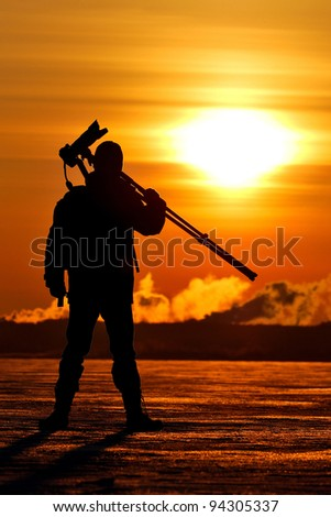 Photographer holding a tripod and camera at the sunrise on a frozen lake, silhouette - stock photo
