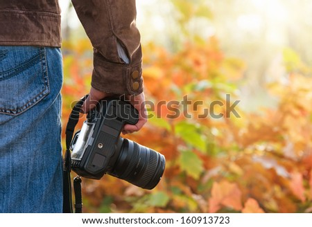 Photographer holding camera outdoors - stock photo