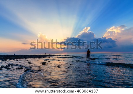 Photographer in action shooting awesome sunrise at Black Stone Beach, Pahang, Malaysia. Ray of light is visible with golden hour and epic clouds. - stock photo