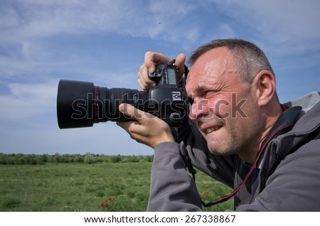 Photographer in action with telephoto lens - stock photo