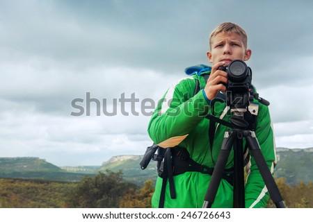 Photographer man in mountain - stock photo