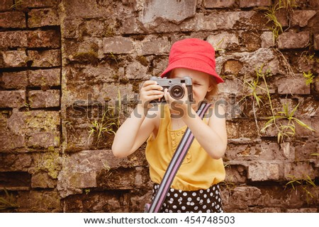 Photographer of school age . To pose for a photo . Camera and child .Walk in the fresh air. The photographer in park . Old brick wall . Children's hobby . Clever child  . The little lady photographs - stock photo