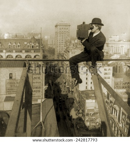 Photographer perched on slender beam 18 stories above pavement of Fifth Avenue, New York City. 1907. - stock photo