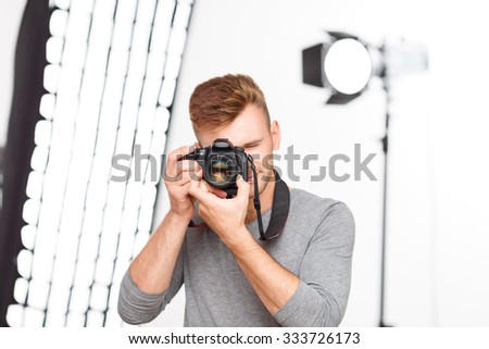 Photographer pose. Young handsome professional photographer stands in the pose of making pictures while holding his camera.  - stock photo