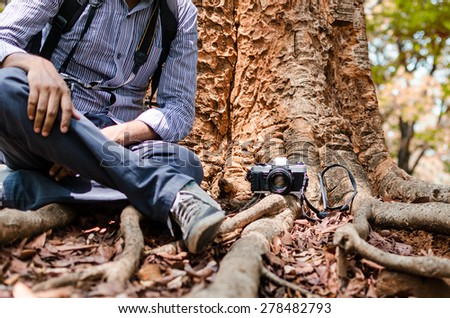 Photographer resting under a big tree with  Film camera in natural outdoor, vintage look - stock photo