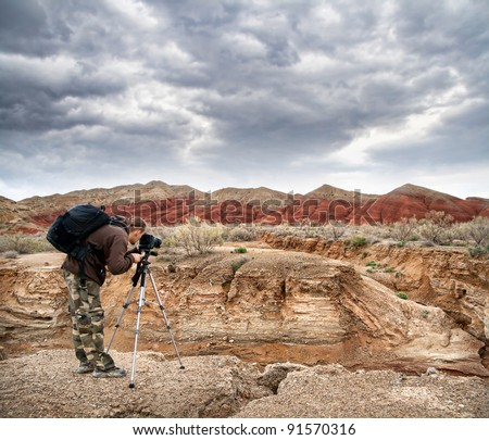 Photographer shooting drought Aktau mountains at dramatic sky background in altyn emel national park in Kazakhstan - stock photo