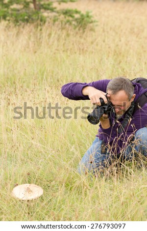 Photographer shooting mushroom with backpack in high grass - stock photo