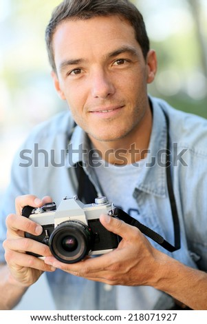 Photographer shooting outside with old camera - stock photo