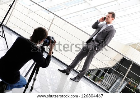 photographer shoots a business man with phone - stock photo