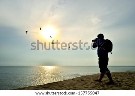 Photographer silhouette shooting near the beach when sun rising - stock photo