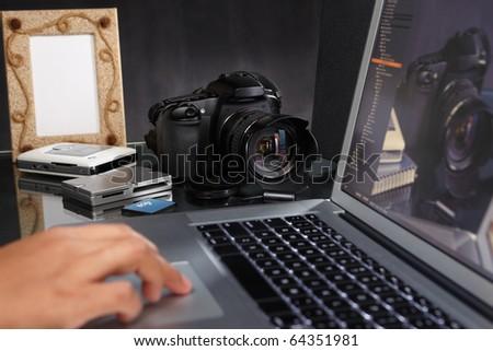 Photographer still working on the photos using laptop - stock photo
