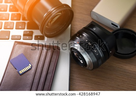 Photographer studio, camera lens, sd cards, power bank, laptop on table.  - stock photo