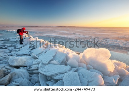 Photographer take pictures on the river bank in winter  - stock photo