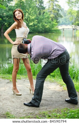 Photographer takes photo of young beautiful brunette woman wearing beige dress at summer green park. - stock photo