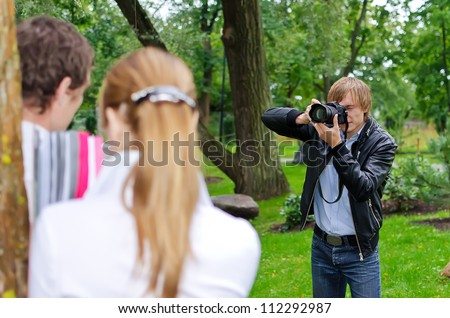 Photographer takes picture of young couple outdoors - stock photo