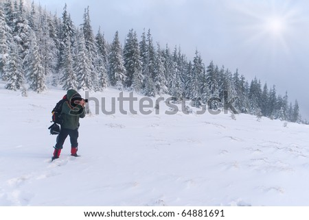 photographer takes pictures in the snowstorm - stock photo