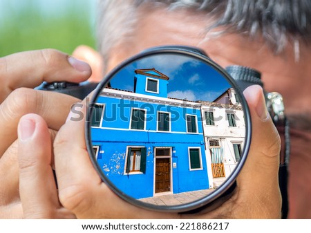 Photographer taking photo with DSLR camera at Burano buildings. Shallow DOF - stock photo