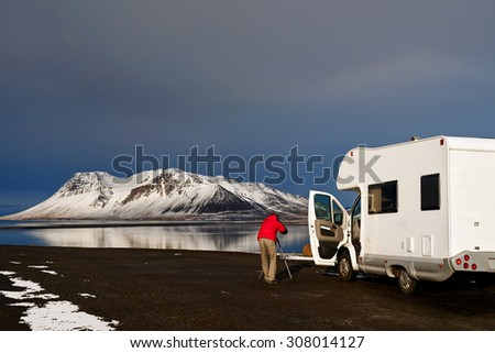 Photographer taking photos of beautiful Icelandic landscape outside mobile motor home RV camper van traveling through Iceland, free and easy holiday - stock photo