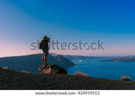 Photographer traveler takes picture caldera and Santorini island in Aegean sea, Greece - stock photo