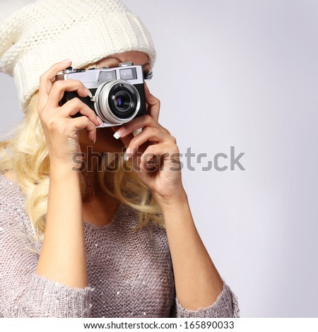 Photographer. Unrecognizable blonde young woman taking photo with vintage film camera in studio - stock photo