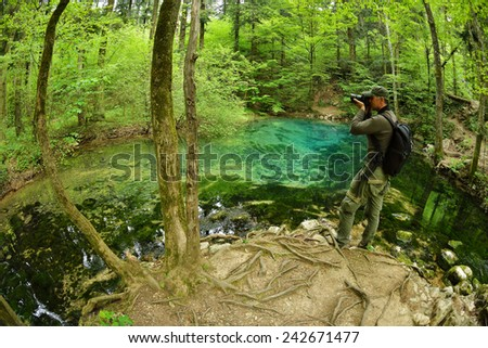 photographer visiting beautiful pond in the woods, Ociul Beiului, Caras Severin county, Romania - stock photo