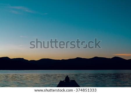 Photographer with a digital camera DSLR shooting pictures of a lake at sunset. - stock photo