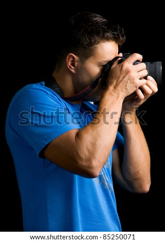 Photographer with camera against black background - stock photo