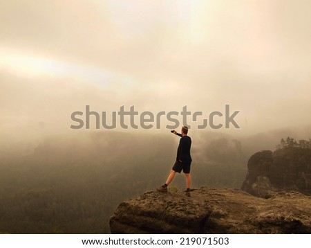 Photographer with camera standing on rocky view point and taking photos of misty morning landscape. National park Saxon Switzerland in Germany. Melancholic autumn morning.  - stock photo