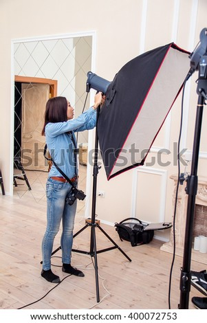 Photographer woman adjusts equipment flash, camera and softbox in the interior photo studio  - stock photo