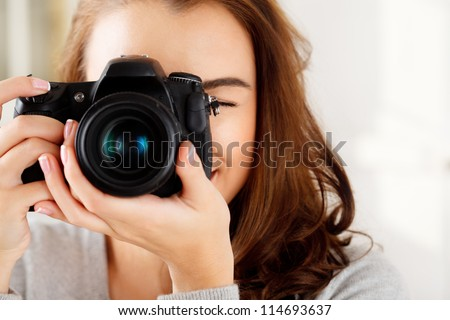Photographer woman girl is holding dslr camera taking photographs - stock photo