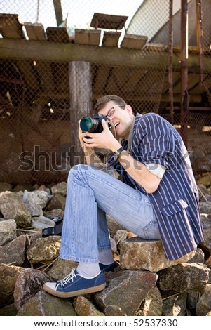 Photographer work with camera on sea bank - stock photo