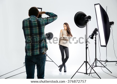 Photographer working with female model in equipped studio - stock photo