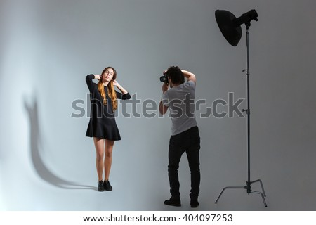 Photographer working with model in studio with equipments - stock photo