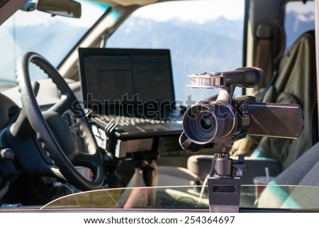 Photographers Gear Van Cockpit Professional Jounalist Video Camera Laptop Computer - stock photo