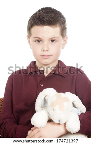 photographic portrait of a boy with sun stuffed bunny both injured - stock photo