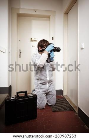 Photographing criminologist technician - stock photo