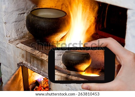 photographing food concept - tourist takes picture of fire hearth of russian stove and old cast iron pot with oven fork on smartphone, - stock photo