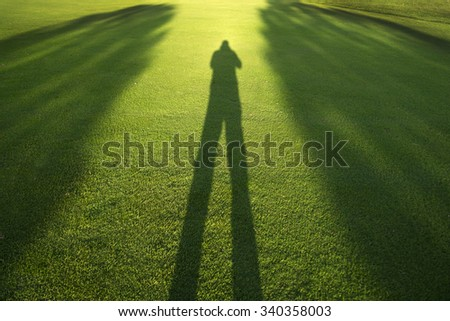 Photographing his own shadow in the late evening on a golf course - stock photo