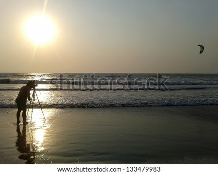 photographing kitesurfers in the rays Sunset - stock photo