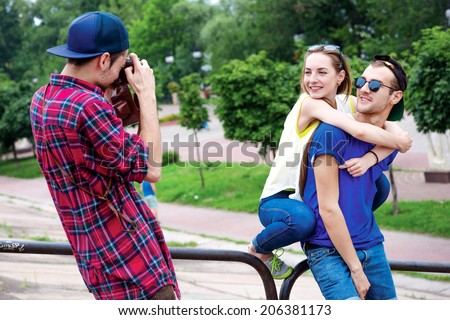 Photographing love story. Young friends have fun together on the street and smile at each other. - stock photo