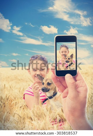 Photographing phone kid with a dog in wheat - stock photo