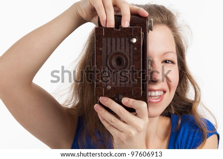 Photographing smiling Woman with old camera - stock photo