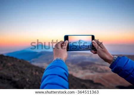 Photographing with smartphone beautiful volcanic landscape with big shadow on the ocean on the sunset - stock photo
