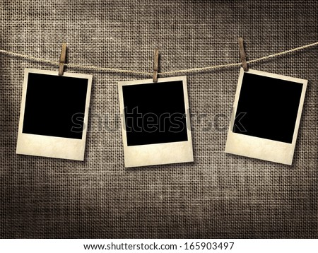 photographs hanging on a clothesline on a linen background - stock photo