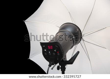 photography studio strobe flash with white umbrella and black copy space - stock photo