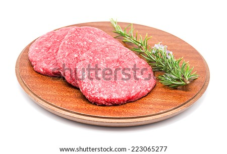 Photography Studio Three raw burgers with a sprig of rosemary on a white background - stock photo