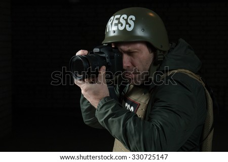 Photojournalist in a helmet and flak jacket wore protective equipment for shooting in the conflict zone - stock photo