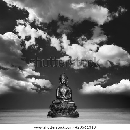 Photomontage: Small figurine of Buddha on wooden desk. Pose of meditation and relaxation. Sky with white bright clouds as metaphor of free mind. Black and white - stock photo
