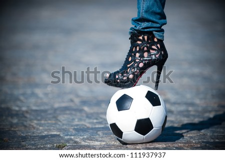 Photos of female feet in shoes with heels on the soccer ball - stock photo